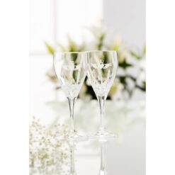pair of galway crystal white wine glasses with claddaghs etched on them in front of flowers